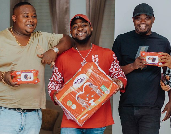 Davido with a pack of mario and Juliet diapers