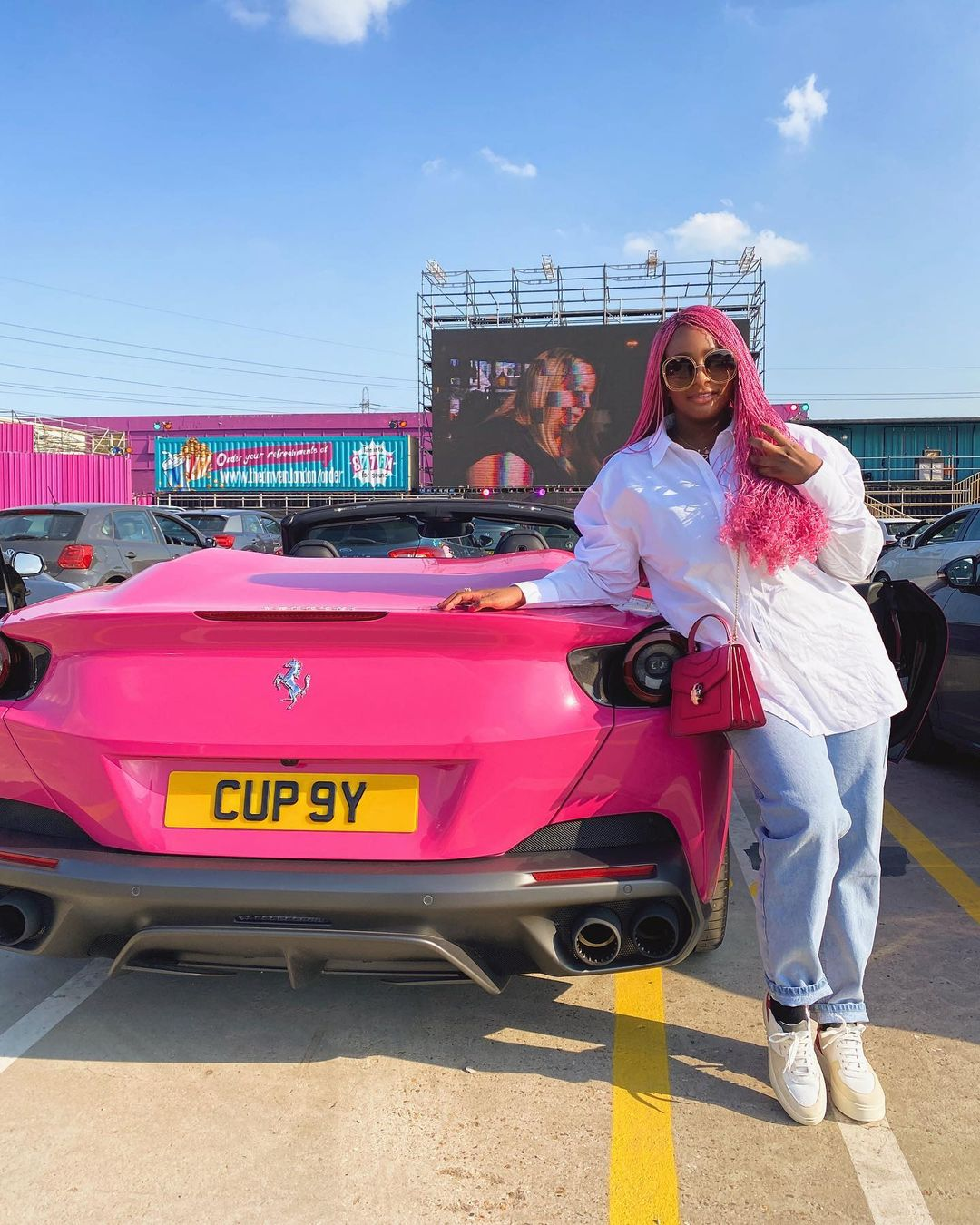 Cuppy posing with one of her Ferrari cars. Source: Instagram @cuppymusic